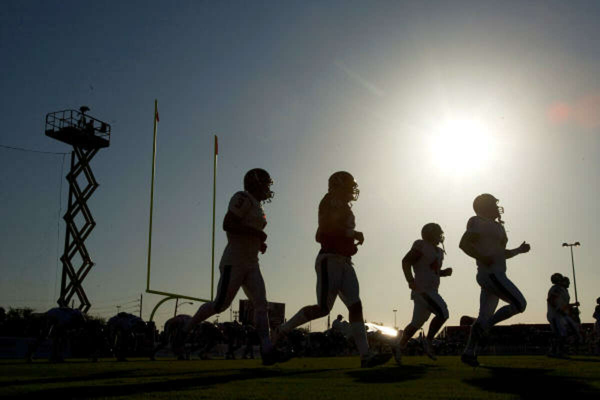 Houston Texans players are silhouetted in the rising sun as they warm up during an NFL football training camp workout.