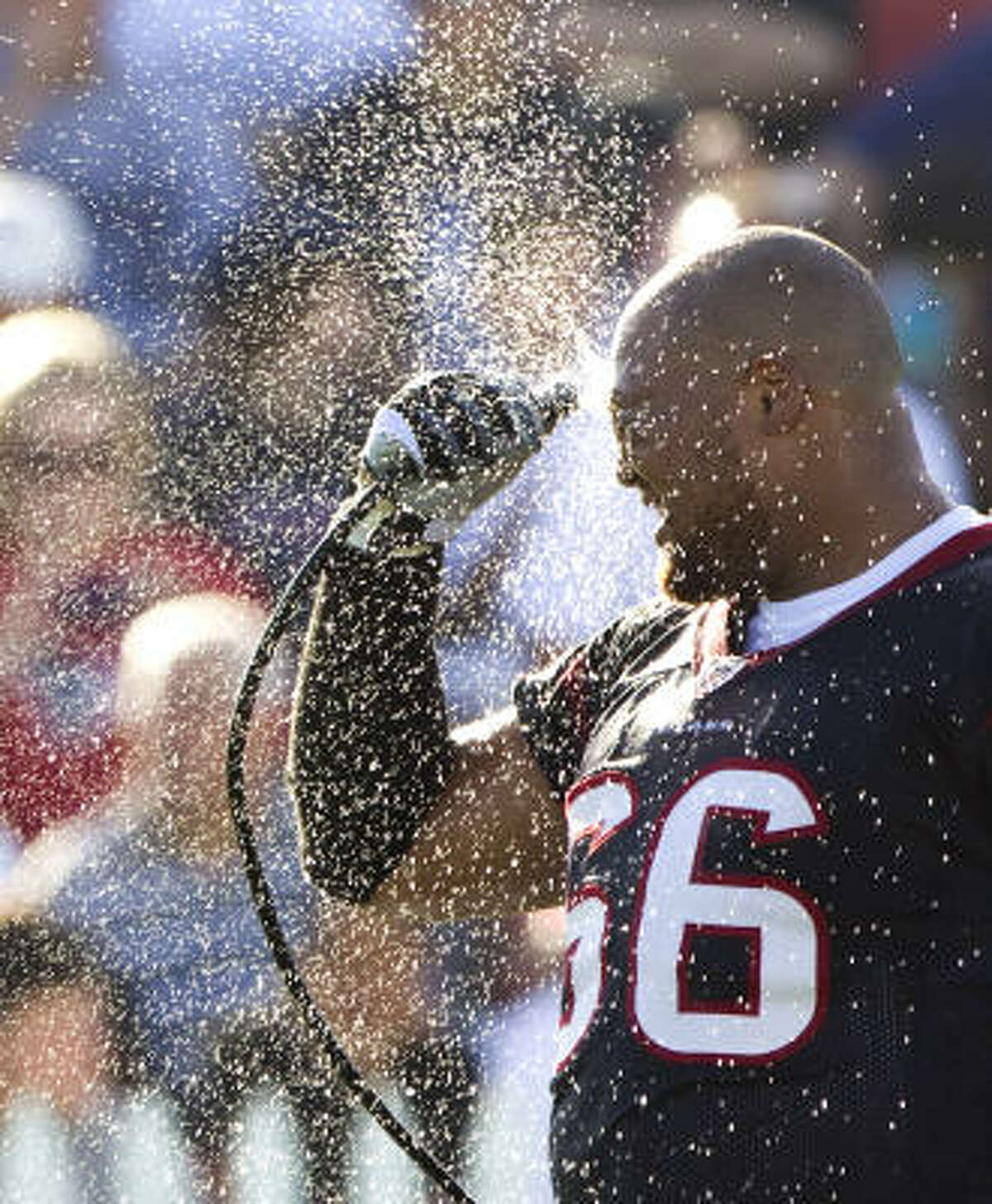 Texans defensive tackle DelJuan Robinson sprays water on his face during training camp.