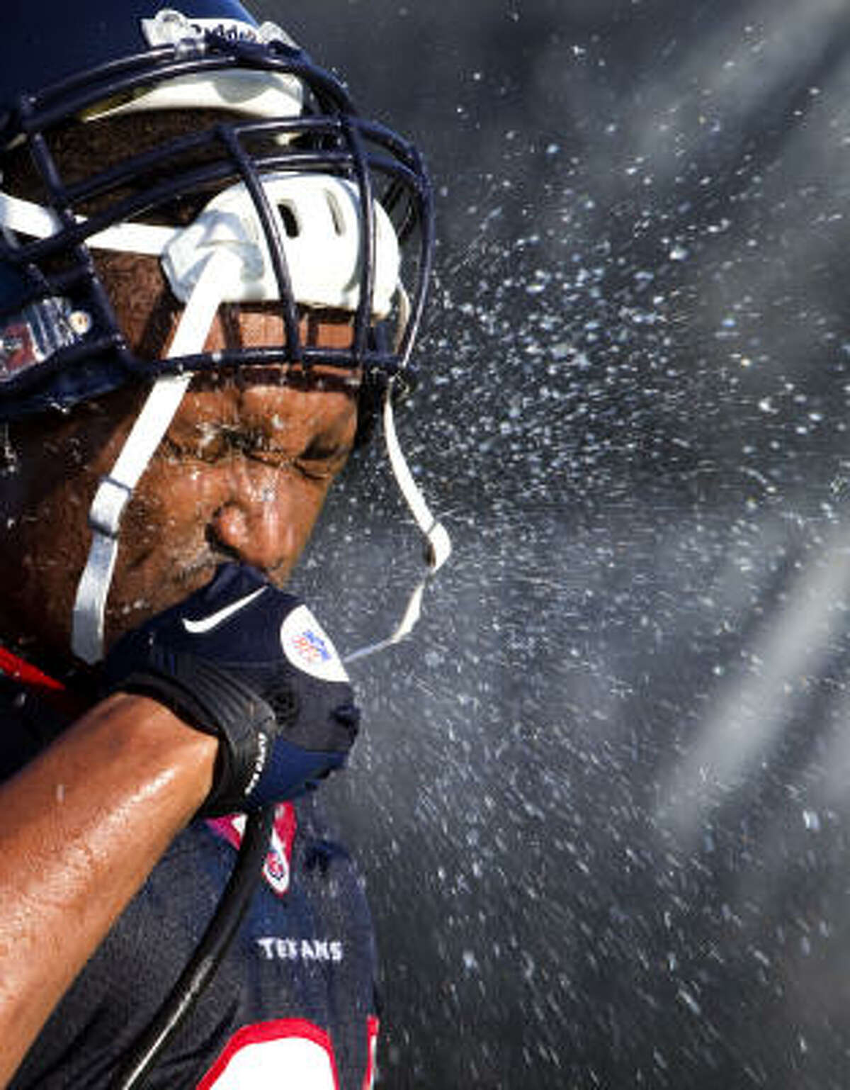 Texans defensive tackle Amobi Okoye takes a water break during a recent workout. When the temperatures rise, the Texans often head into the comfort of their practice bubble at Reliant Park.