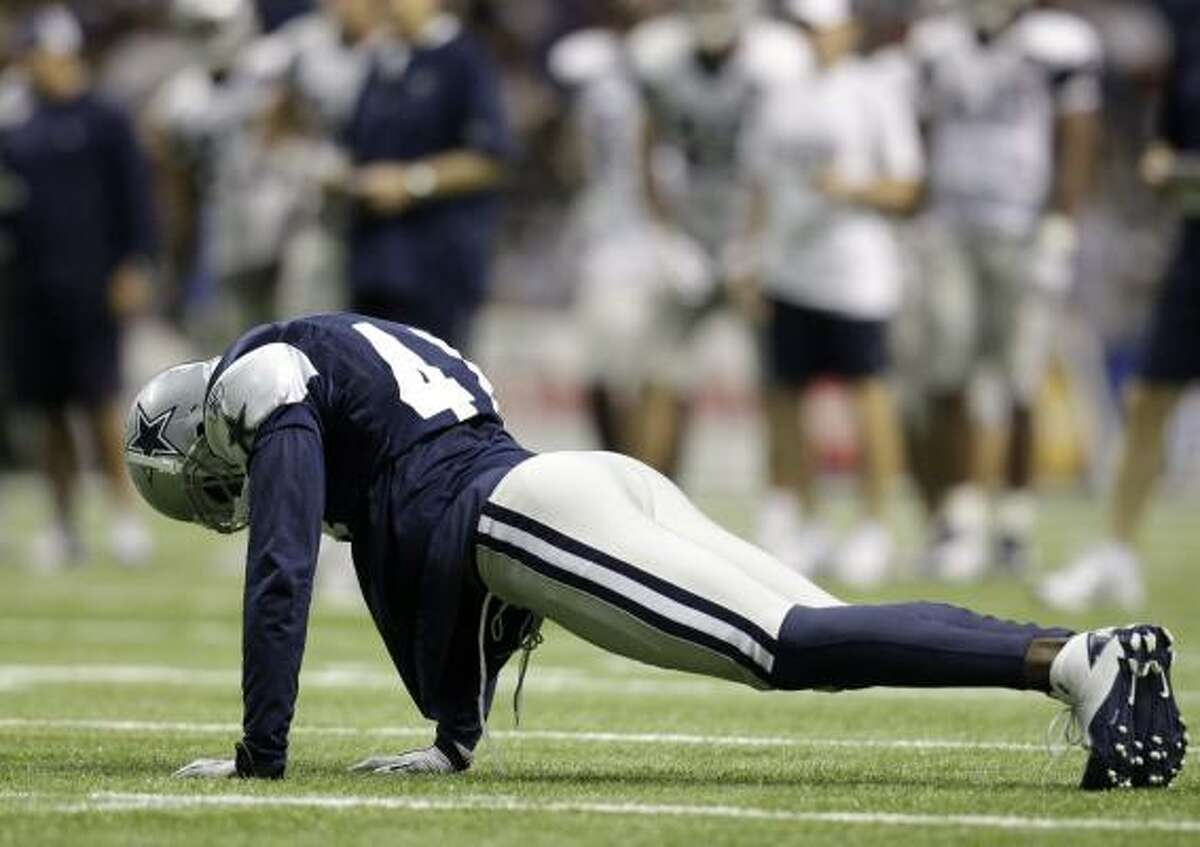 Cowboys cornerback Terence Newman gets down to do a set of push-ups after covering on a play.
