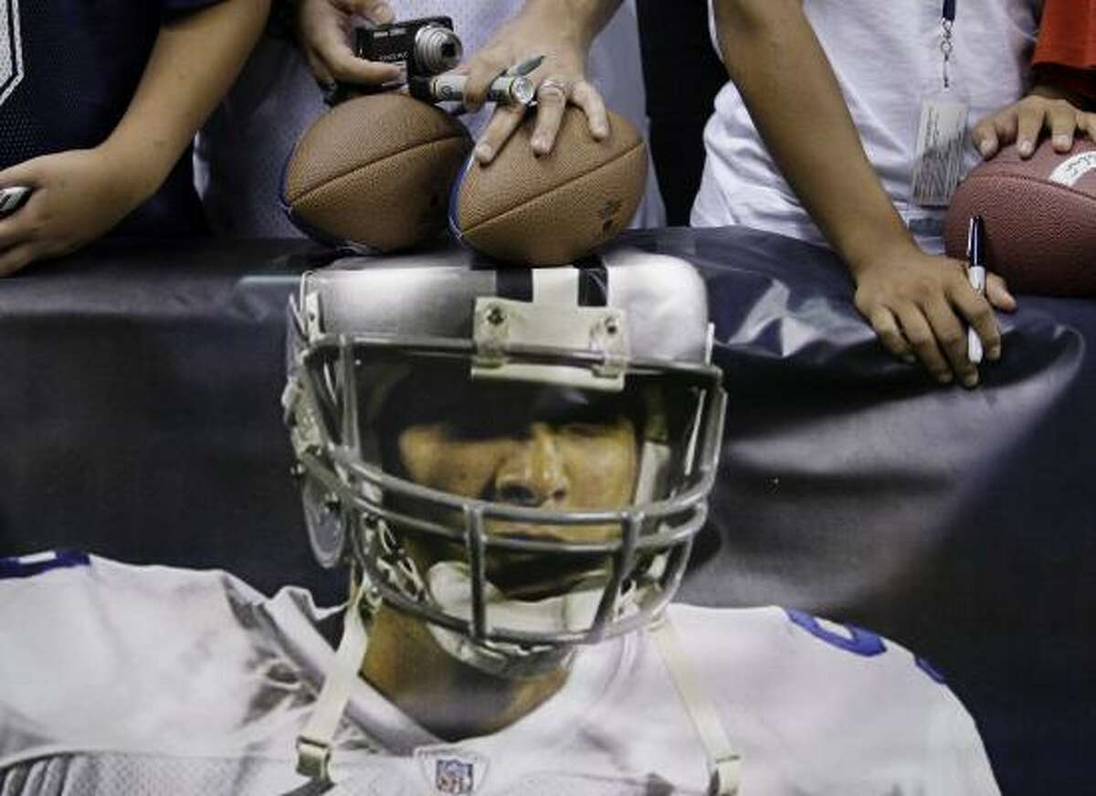 Fans with footballs, markers and cameras wait for autographs, next to a poster of Dallas Cowboys quarterback Tony Romo.