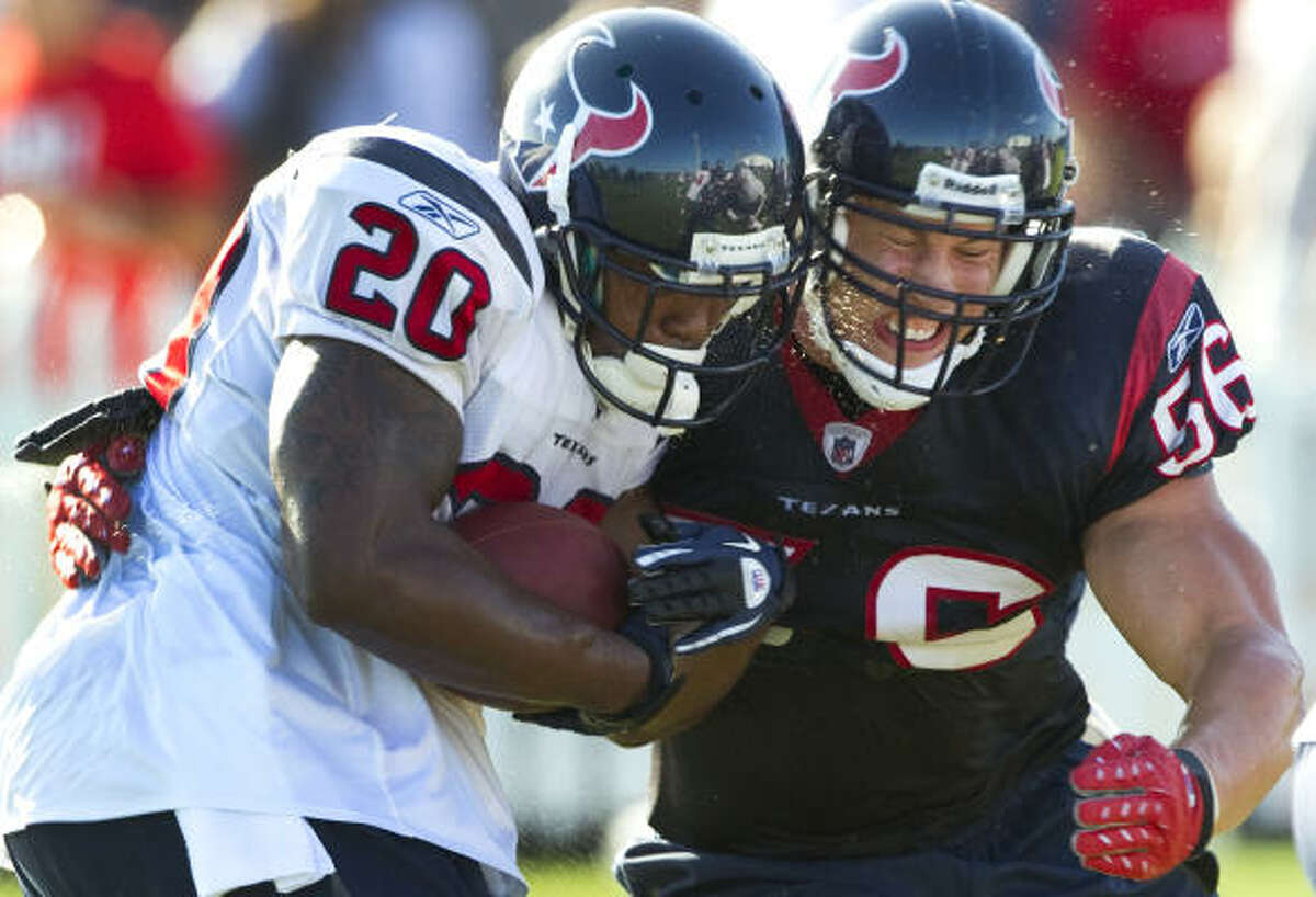 Texans running back Steve Slaton, left, and linebacker Brian Cushing collide during a drill. Slaton is competing to get his starting job back.