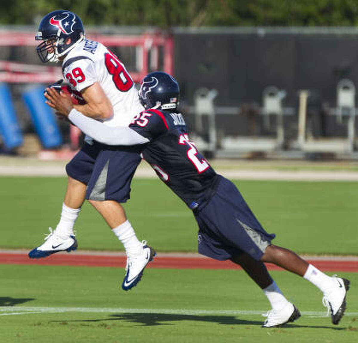 Texans wide receiver David Anderson leaps in front of cornerback Kareem Jackson to catch a pass.