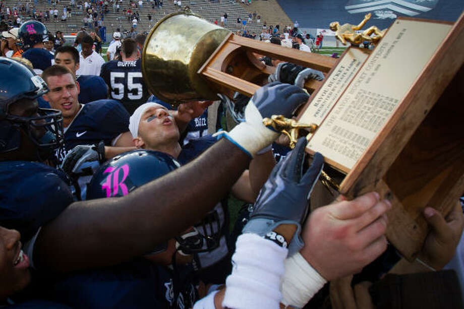 Rice players, including running back Sam McGuffie (2), center, celebrate with the Bayou Bucket trophy after defeating UH on Saturday. Photo: Smiley N. Pool, Houston Chronicle