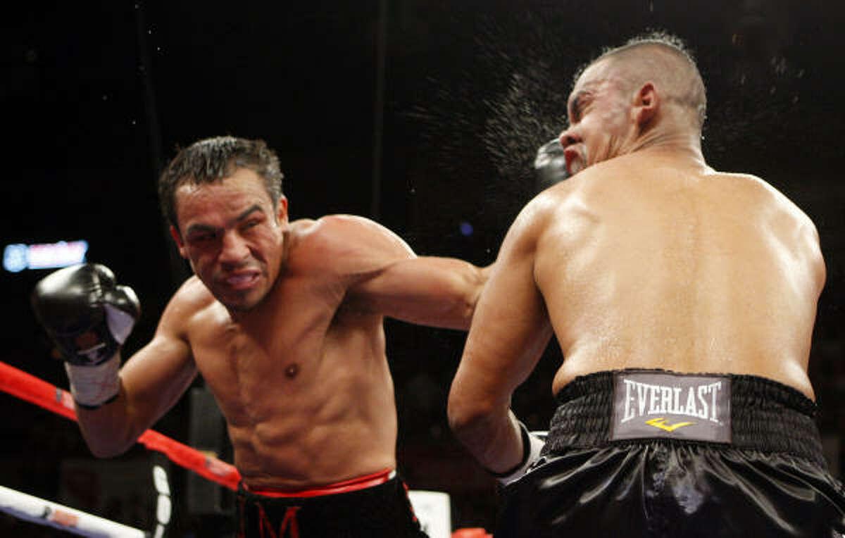 Juan Manuel Marquez, left, of Mexico, punches Juan Diaz. Marquez won by unanimous decision.