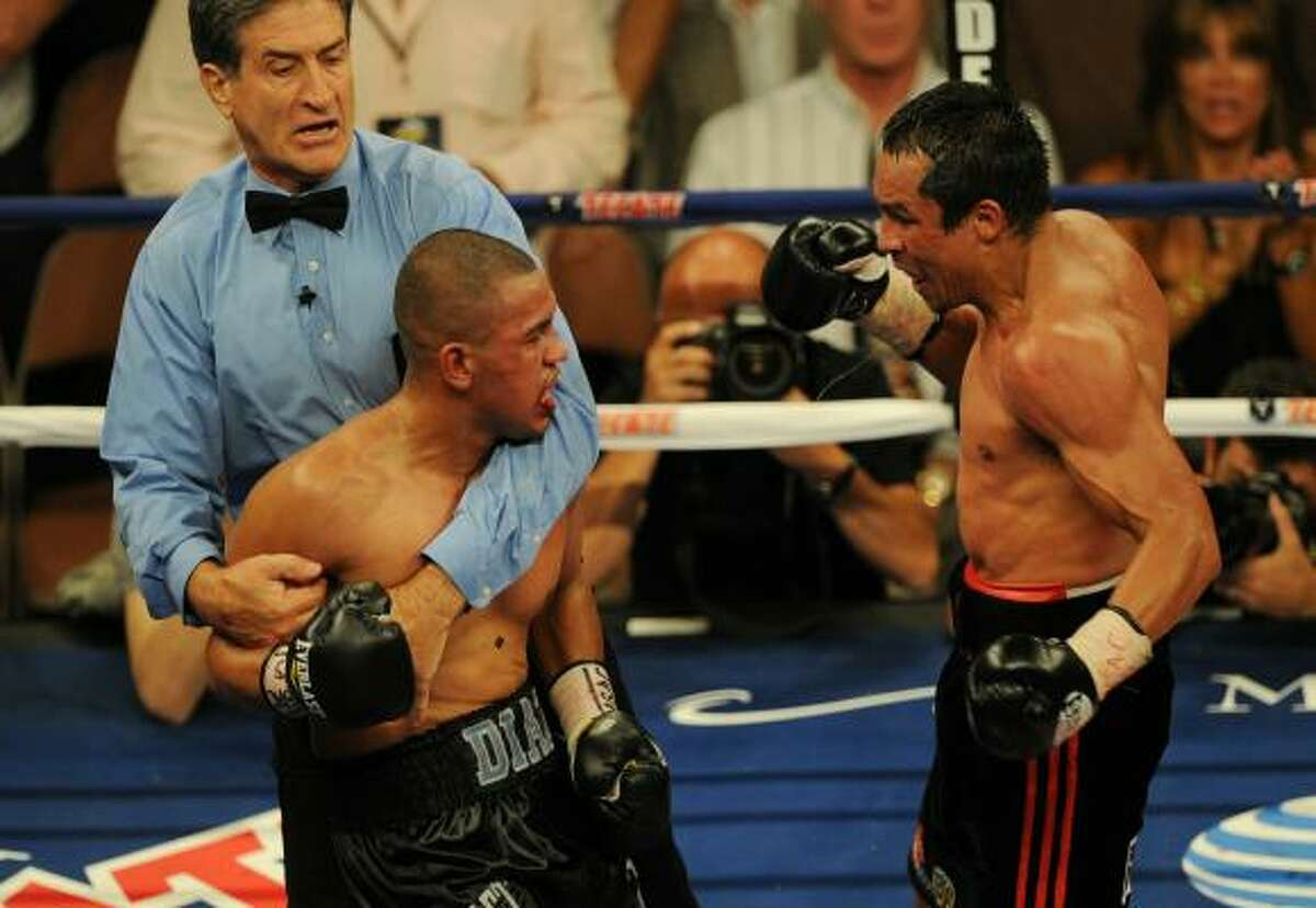 Juan Manuel Marquez, right, prepares to land a punch on Juan Diaz as the referee tries to stop the fight. Mexican veteran Juan Manuel Marquez won the fight and was defending his lightweight title against Diaz in a rematch of their title slugfest from last year.