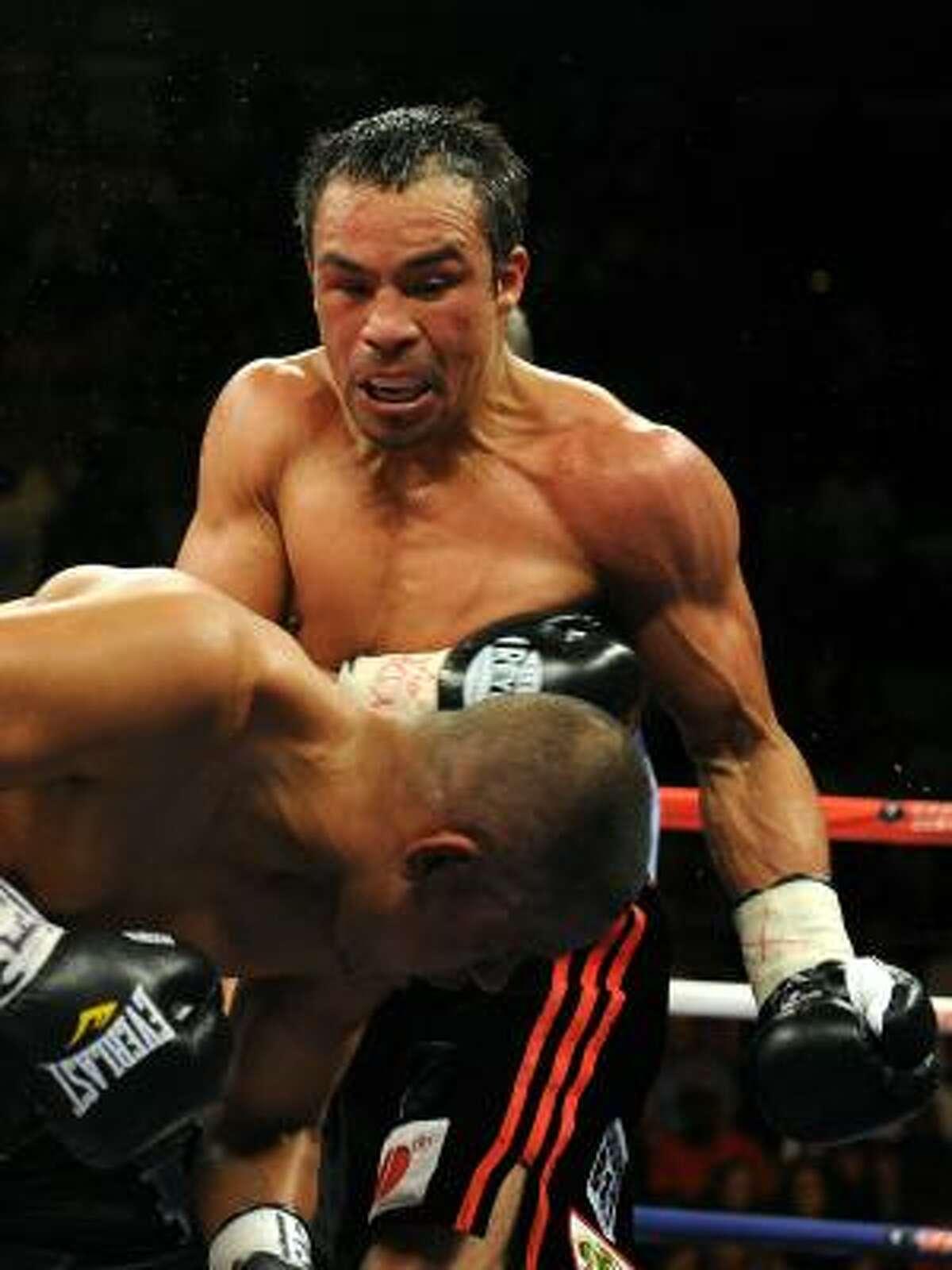 Juan Manuel Marquez of Mexico, top, punches Juan Diaz.