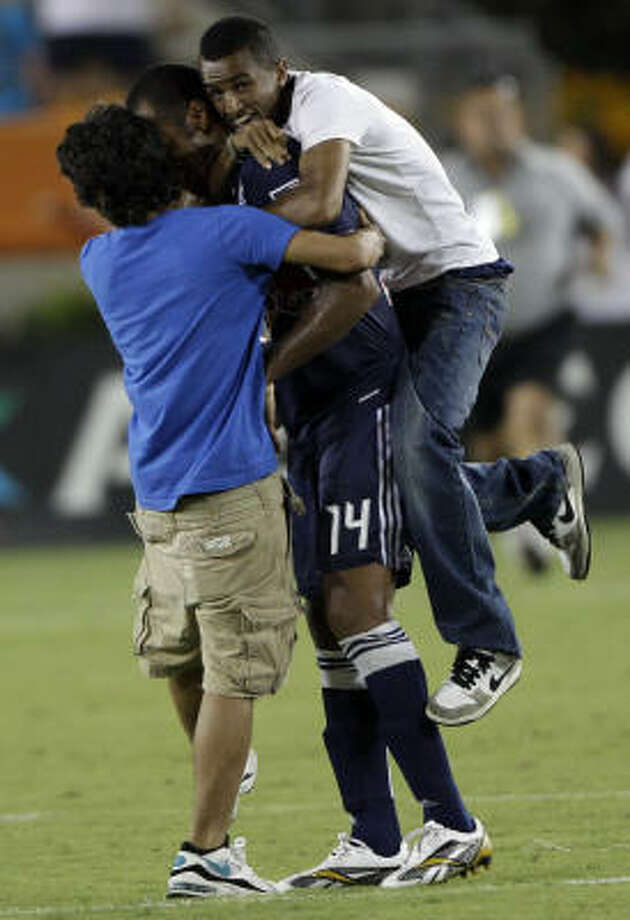 Fans run onto the field and grab New York Red Bulls striker Thierry Henry during the second half. Both fans were caught and escorted from the field by security. The Red Bulls tied the Dynamo 2-2. Photo: David J. Phillip, AP