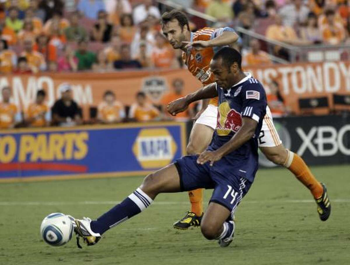 Red Bulls striker Thierry Henry takes a shot on goal as Dynamo defender Eddie Robinson runs for the ball.