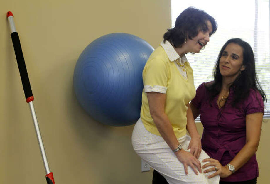 Helms exercises with physical therapist Claudia Puett in the Woodlands. Helms hopes to walk again. Photo: Yasmeen Smalley, Chronicle