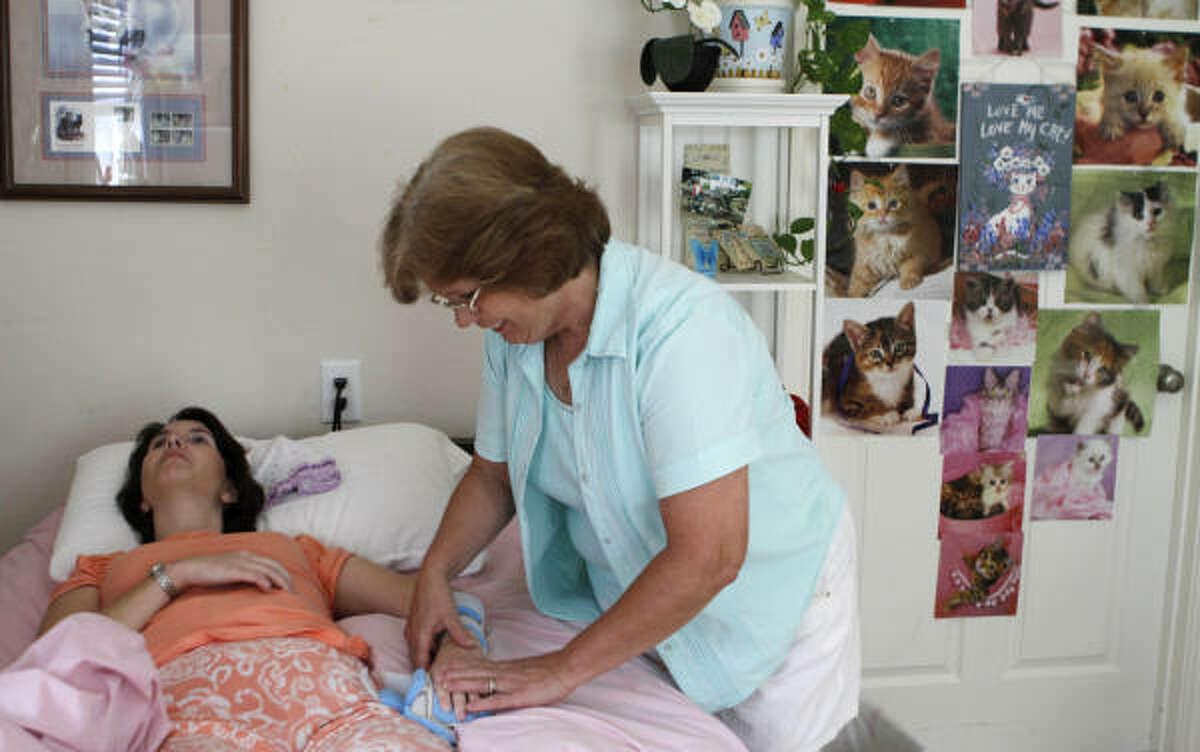 DuChemin adjusts Helms' arm brace in Helms' Conroe room, which displays photos of Helms' daughter, Leanne.