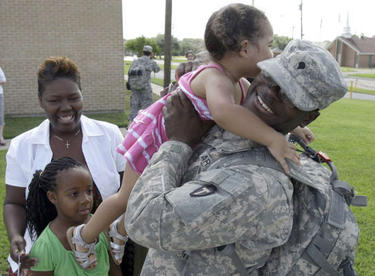 Spc. Chadwick Chevannes of Katy hugs his sister, Maya Chevannes, 2, during a reunion with his mom, Michelle Chevannes, and other sister, Michah Chevannes, 8, as the Alpha 72nd Brigade Special Troops Battalion has a reunion after returning from Iraq.