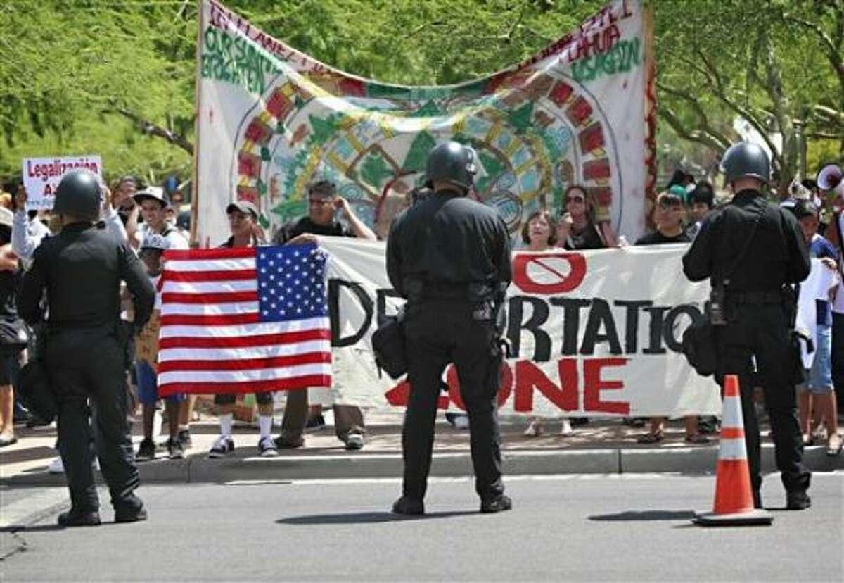 Policías custodian una calle en Phoenix el jueves 29 de julio del 2010 mientras manifestantes protestan contra la nueva ley migratoria SB1070 de Arizona. El fallo cautelar que suspendió la aplicación de gran parte de la estricta ley puede interpretarse como una victoria del gobierno federal demócrata y una derrota para la gobernadora republicana Jan Brewer, pero ninguno de los dos partidos está seguro de quién podrá sacar rédito al tema.