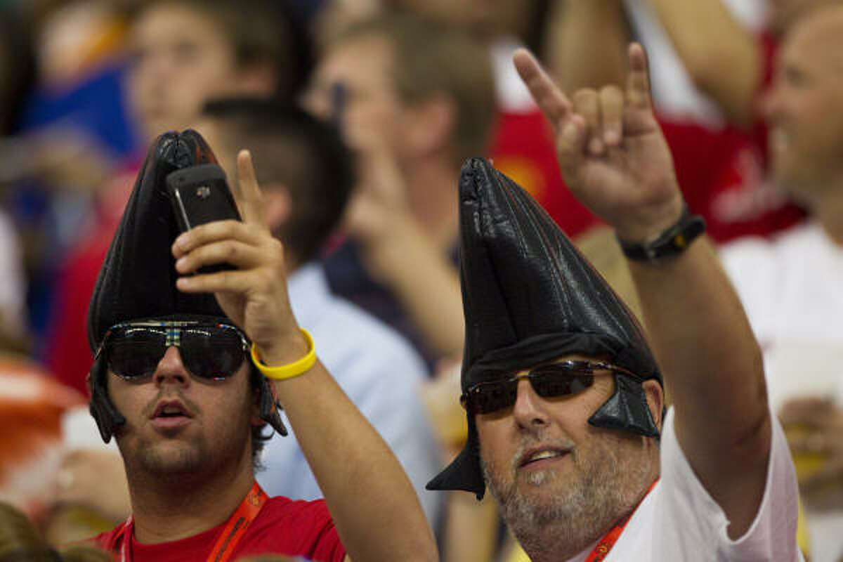 Soccer fans wearing Elvis wigs cheer during the first half.