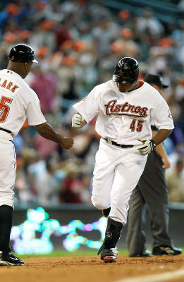 Astros left fielder Carlos Lee celebrates his two-run home run with third base coach Dave Clark during the sixth inning. Photo: Karen Warren, Chronicle