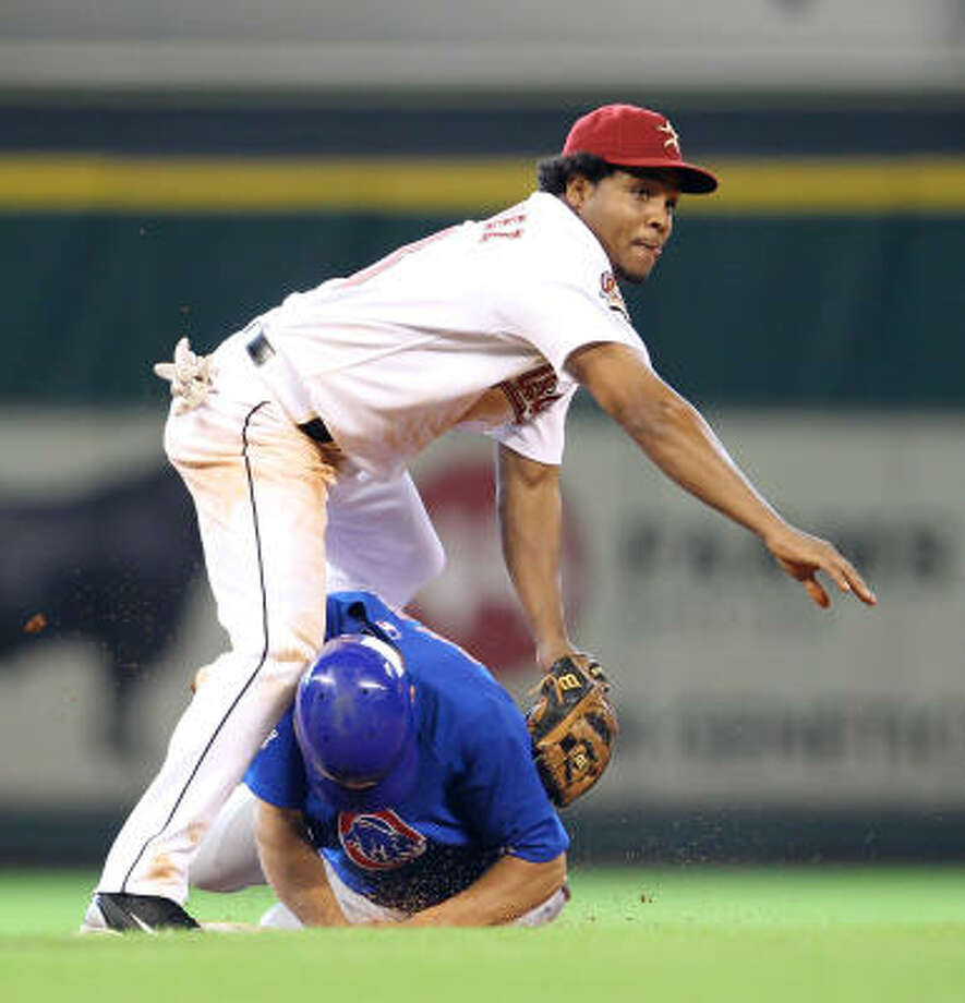 Astros shortstop Anderson Hernandez falls over Cubs outfielder Tyler Colvin after throwing him out on a double play during the eighth inning. Photo: Karen Warren, Chronicle