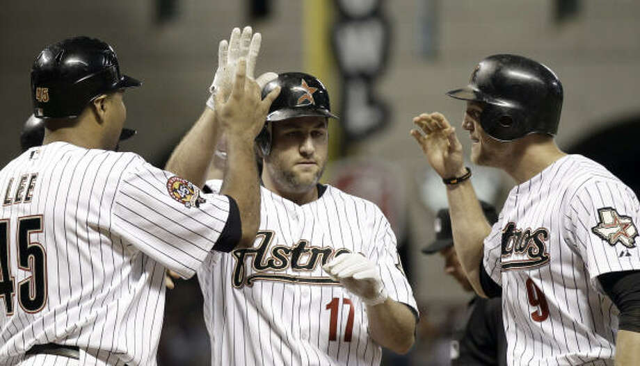 Lance Berkman, center, is congratulated by teammates Hunter Pence, right, and Carlos Lee after they and Jeff Keppinger all scored on Berkman's grand slam in the seventh inning. Photo: David J. Phillip, AP
