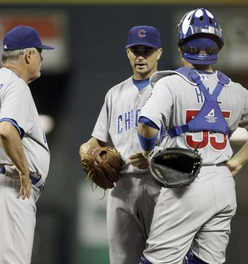 Cubs manager Lou Piniella, left, pulls pitcher Ted Lilly, center, from the game as catcher Koyie Hill joins them on the mound with one out left in the sixth inning. Photo: David J. Phillip, AP