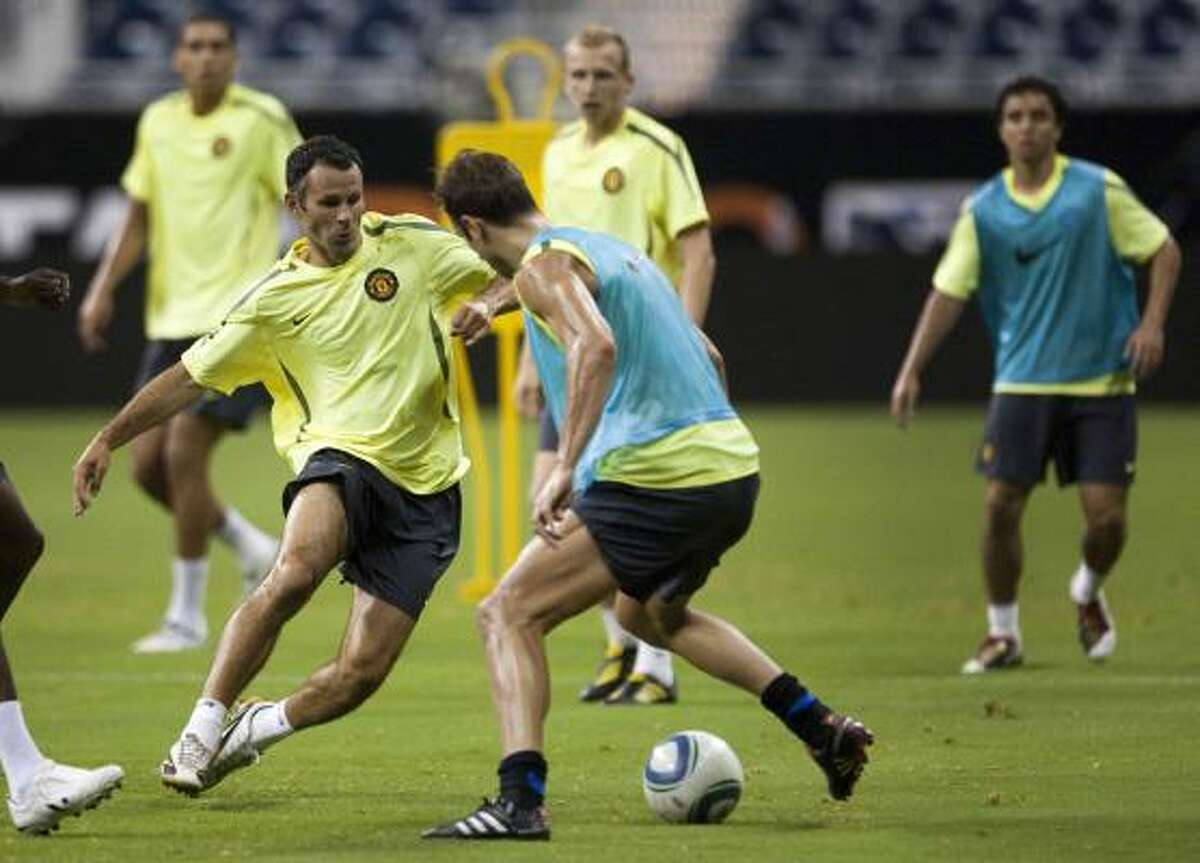 Manchester United midfielder Ryan Giggs, left, works against a teammate during Tuesday's practice.