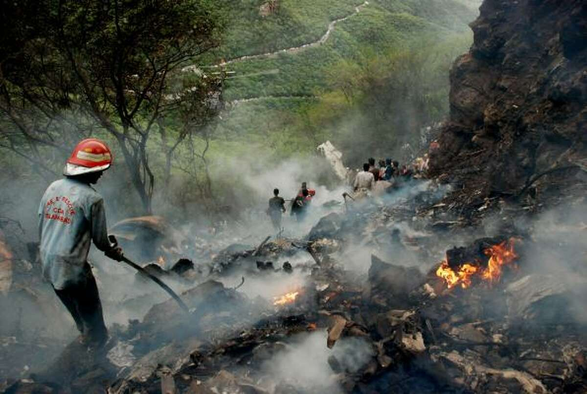 Pakistani rescue workers search for survivors in wreckage of a crashed passenger plane at The Margalla Hills on the outskirts of Islamabad on July 28, 2010.