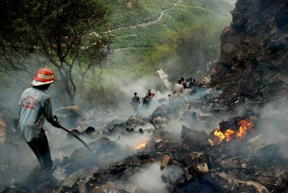 Pakistani rescue workers search for survivors in wreckage of a crashed passenger plane at The Margalla Hills on the outskirts of Islamabad on July 28, 2010. Photo: ADIL KHAN, AFP/Getty Images