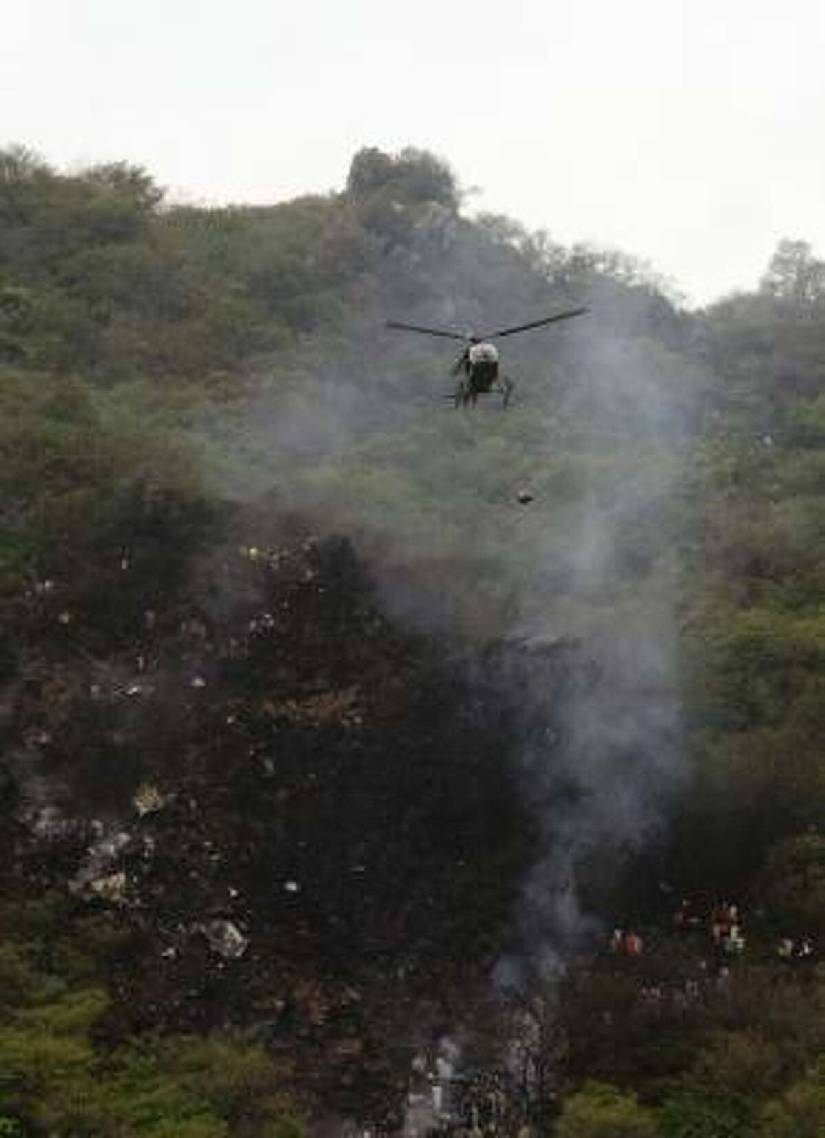 A Pakistani military helicopter carries victims' remains from the site of a passenger plane crash in the Margala Hills on the outskirts of Islamabad on July 28, 2010.