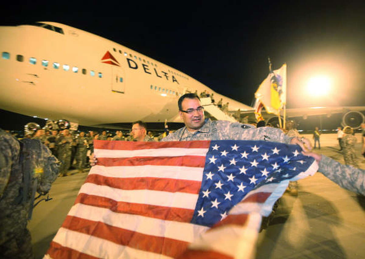 Spc. Thomas Lacy, 72nd's IBCT Bravo-536 BSB, of San Antonio, waves an American flag upon arrival to Biggs Army Airfield in El Paso. The Texas National Guard's 72nd Infantry Brigade Combat Team returned to Texas from a 9-month deployment to Iraq, but before going home they need to debrief at Fort Bliss.