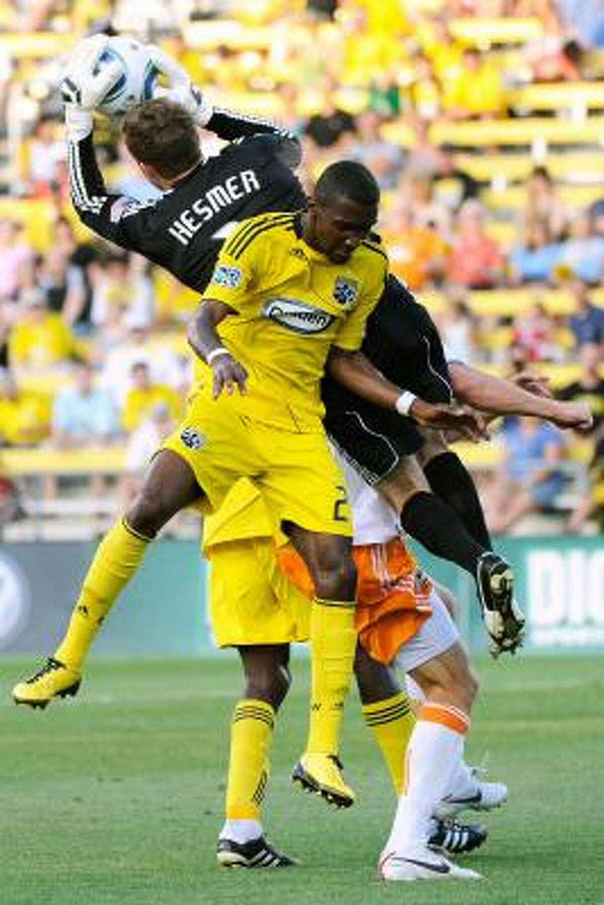 Columbus Crew goalkeeper William Hesmer splits through his teammate Shaun Francis and a Dynamo player to make a save.