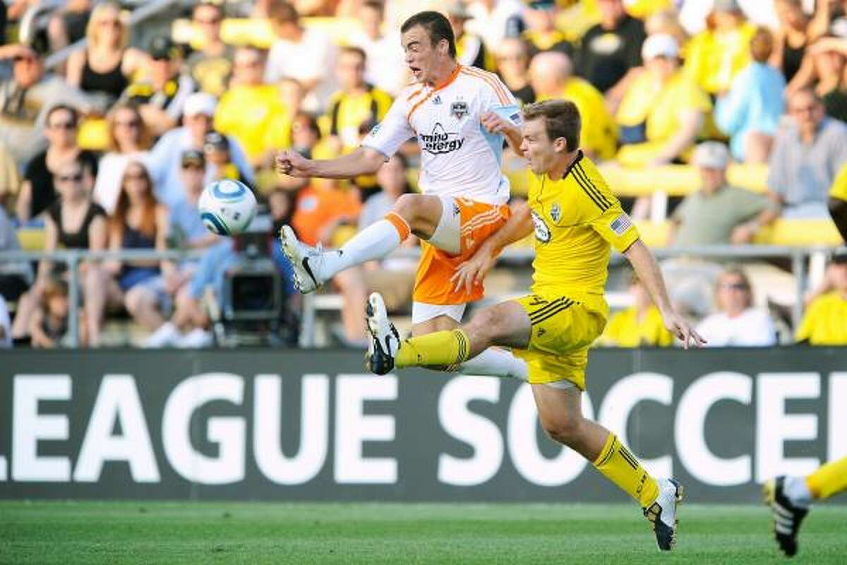Dynamo forward Cam Weaver beats Crew defender Chad Marshall to the ball in the first half.