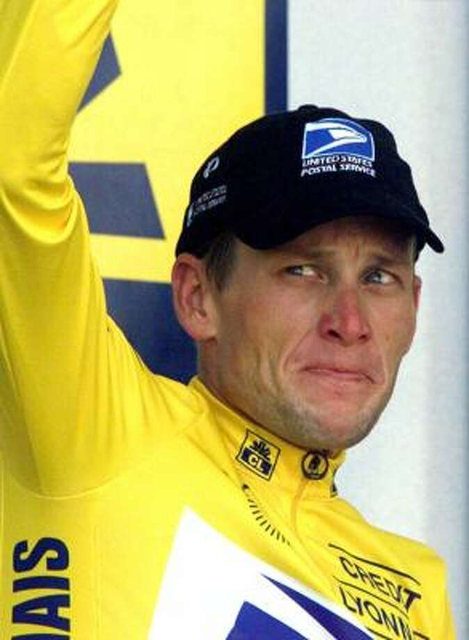 Lance Armstrong grimaces on the podium as he retains the overall leader's yellow jersey after the 13th stage of the 1999 Tour de France. Photo: LAURENT REBOURS, AP