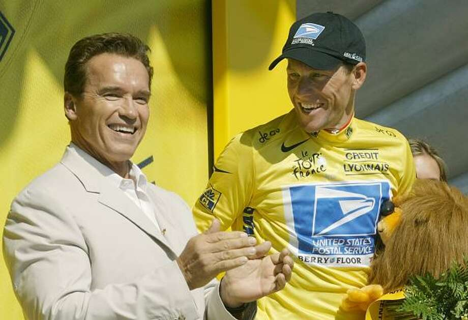 Overall leader Lance Armstrong, right, looks at American star Arnold Schwarzenegger after putting on the yellow jersey on the podium after the 11th stage of the 2003 Tour de France. Photo: LAURENT REBOURS, AP