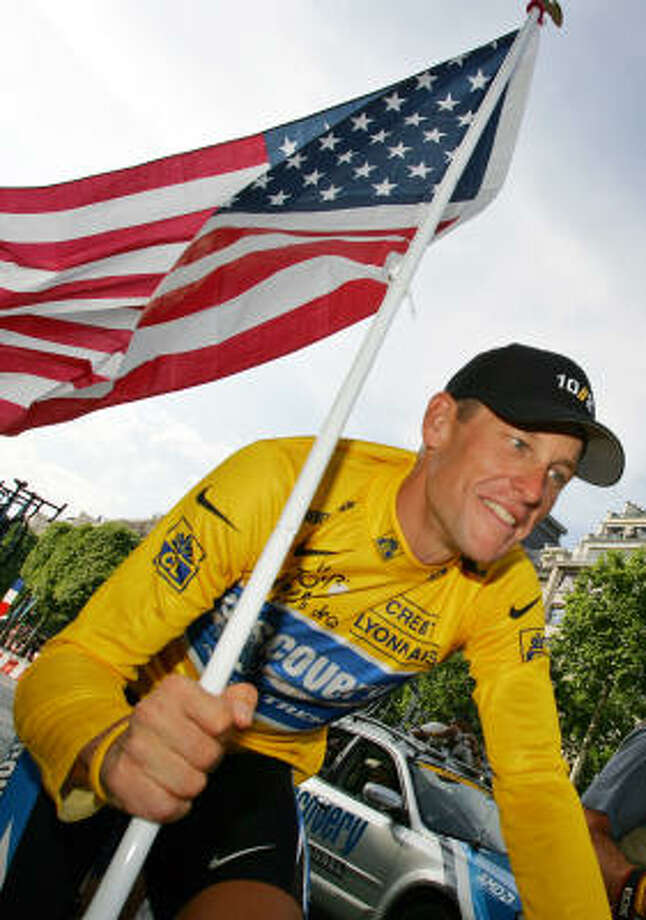 Lance Armstrong carries the United States flag during a victory parade on the Champs Elysees avenue in Paris, after winning his seventh straight Tour de France in 2005. In winning seven consecutive Tours from 1999-2005, Armstrong made history, obliterating the previous record of five victories. Photo: PETER DEJONG, AP