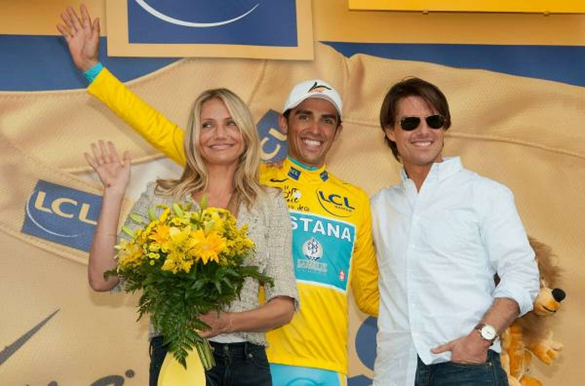 Actress Cameron Diaz, left, and actor Tom Cruise, right, stand on the podium with cyclist Alberto Contador after he was presented the yellow jersey.