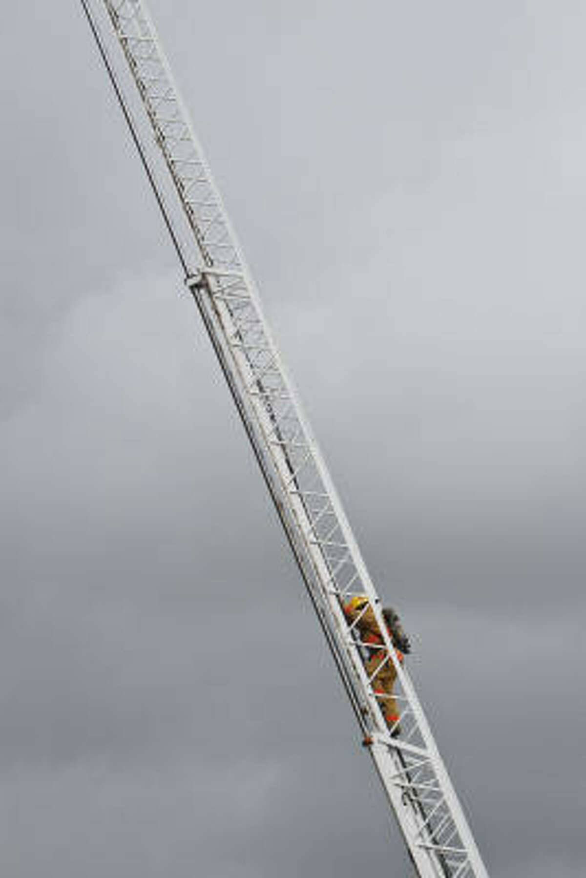 Camilo Bello climbs up an 80-foot ladder during a firefighting exercise.