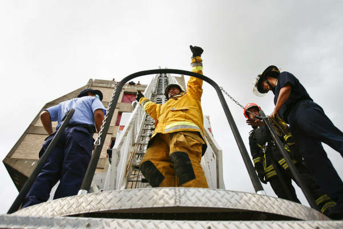 Fernando Jizarazo celebrates after successfully climbing an 80-foot ladder during a firefighting exercise for 30 firefighters from Latin America and the Caribbean.