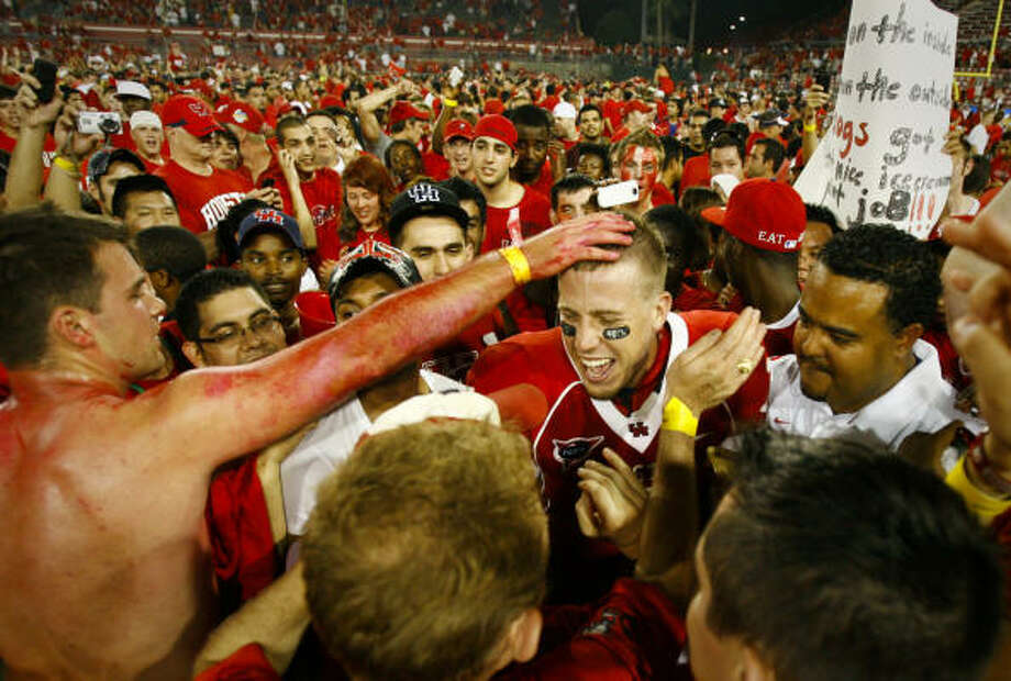 Sept. 26 | University of Houston quarterback Case Keenum celebrates with fans who rushed the field after the Cougars beat Texas Tech 29-28 at Robertson Stadium. Photo: Nick De La Torre, Houston Chronicle