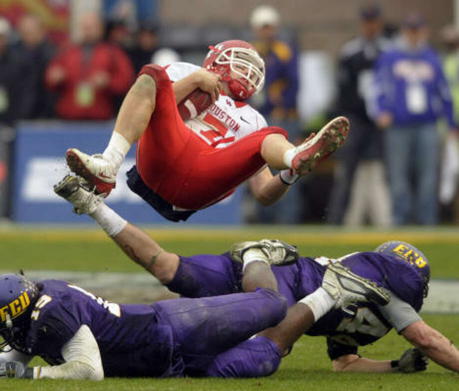 Houston's quarterback Case Keenum (7) dives over East Carolina's Chris Mattocks (19) and Nick Johnson (44)  during the second half of the NCAA college football Conference USA championship game in Greenville, N.C., Saturday, Dec. 5, 2009. East Carolina won 38-32. Photo: Sara D. Davis, AP