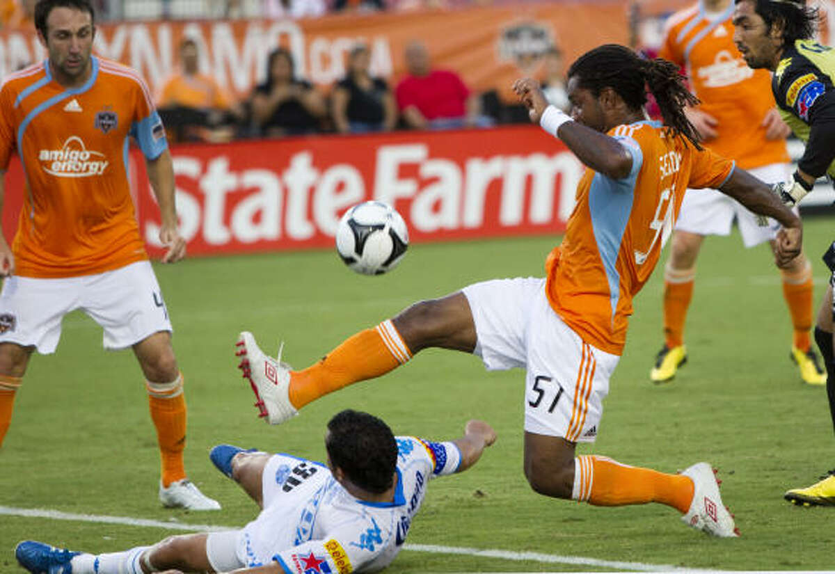 Dynamo defender Adrian Serioux tries a shot over Puebla forward Felipe Ayala during the first half of Wednesday's SuperLiga match at Robertson Stadium. The Dynamo won 1-0 to advance to the SuperLiga semifinals.