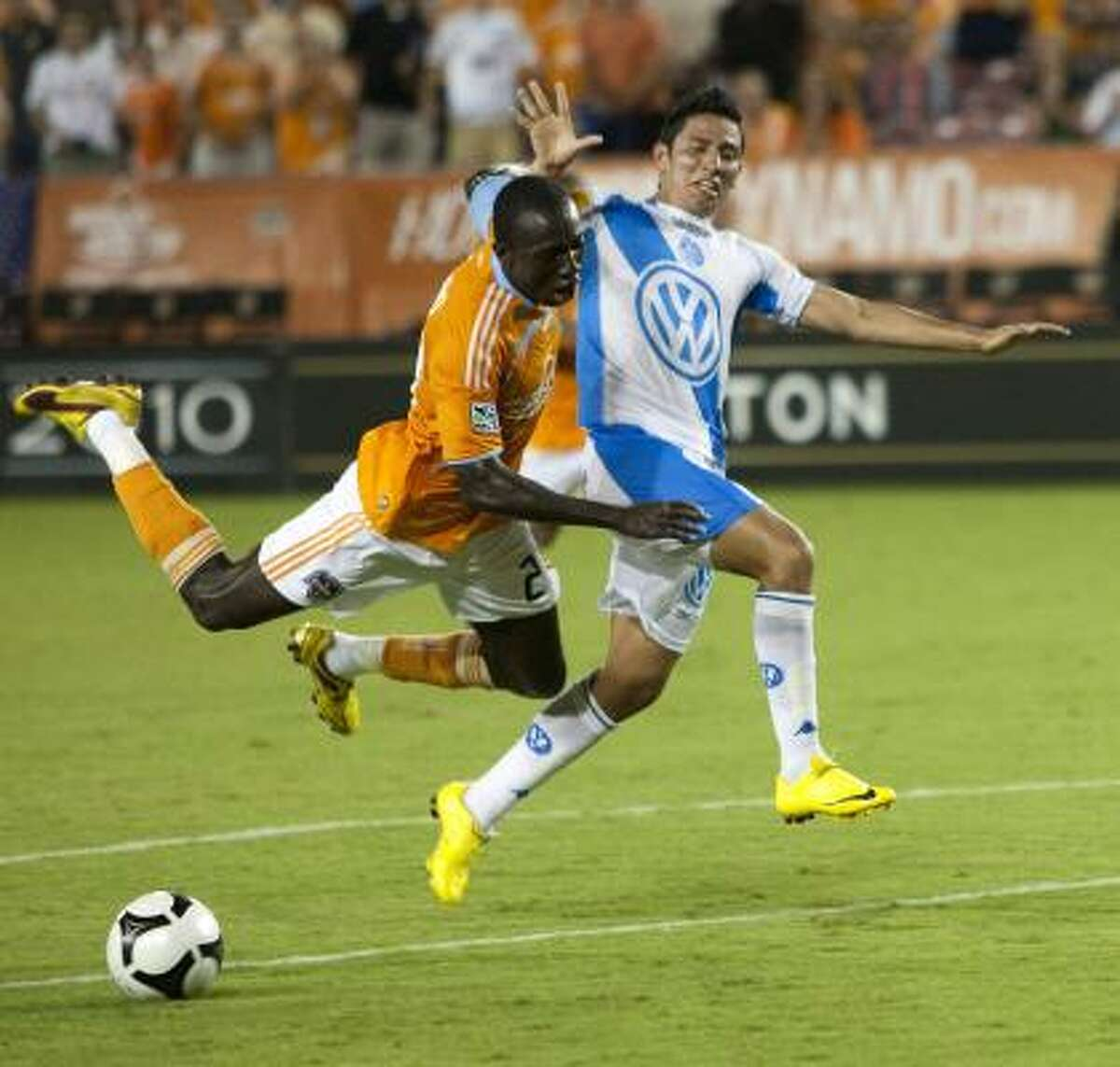 Dynamo midfielder Dominic Oduro, left, collides with Puebla defender Orlando Rincon as Oduro wins on a breakaway to the goal during the second half. Orduro was given a red card on the play and ejected from the game.