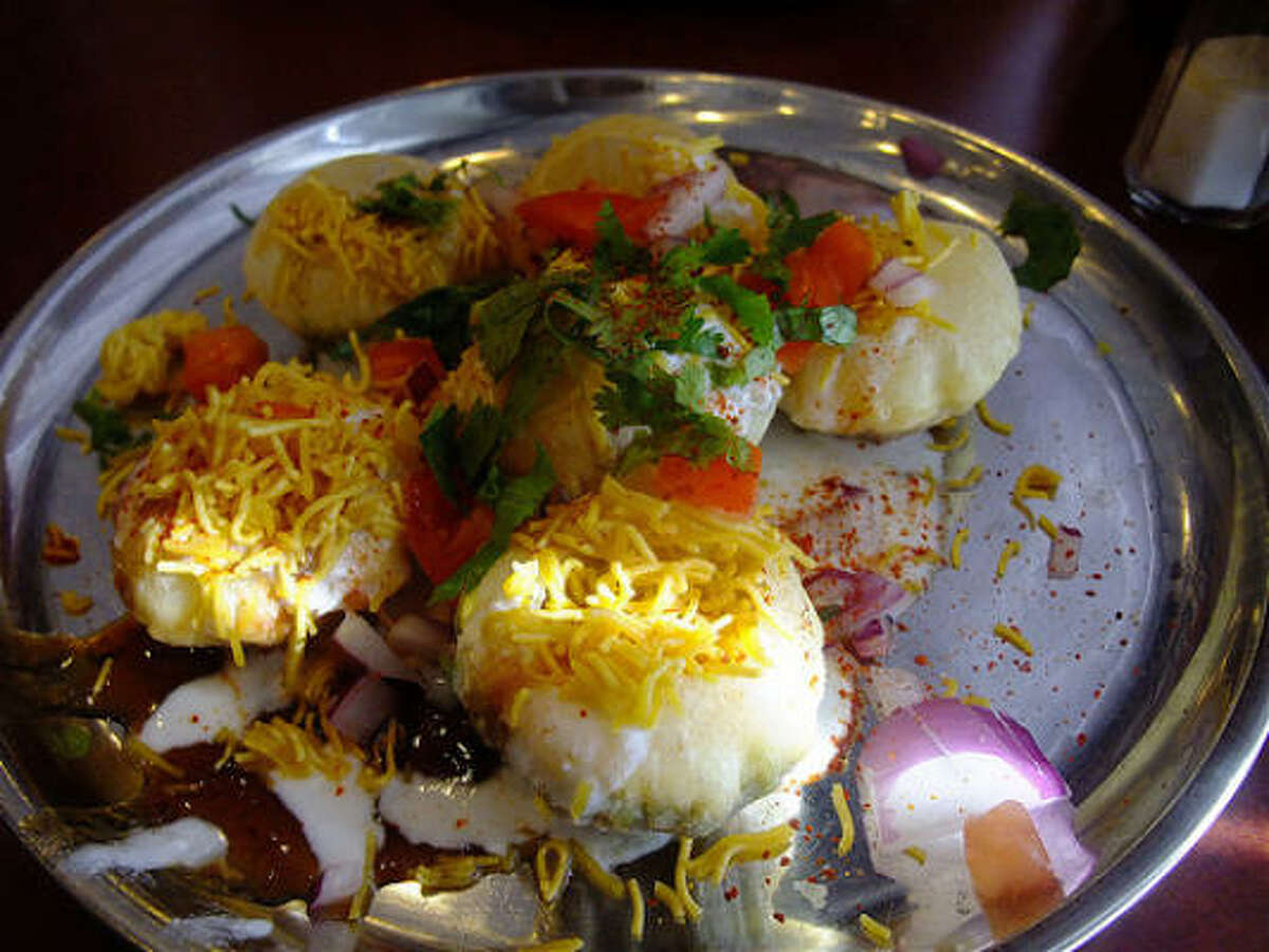 Dahi puri at Shri Balaji Bhavan. Hollow lentil-flour crisps are filled with potato, chick peas, yogurt and tamarind chutney, then showered with sev (crisp fried noodles), cilantro, tomato, onion and hot red pepper.