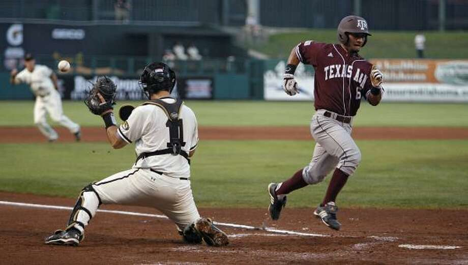 Texas A&M's Andrew Collazo scores in front of Missouri catcher Brett Nicholas. Photo: Chris Landsberger, AP
