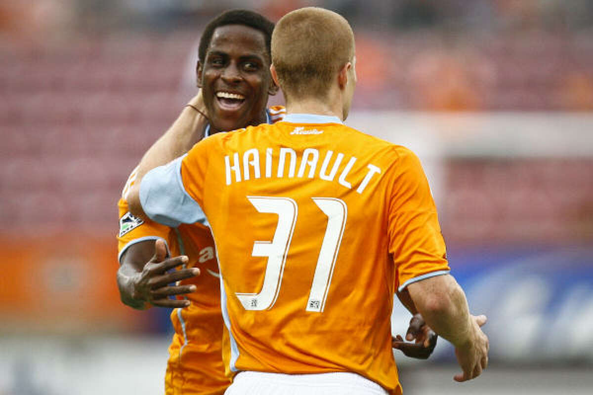Dynamo midfielder Lovel Palmer, left, celebrates with teammate Andrew Hainault after scoring in the sixth minute of Sunday's SuperLiga group stage match against Chivas USA on Sunday at Robertson Stadium. The game ended in a 1-1 draw.
