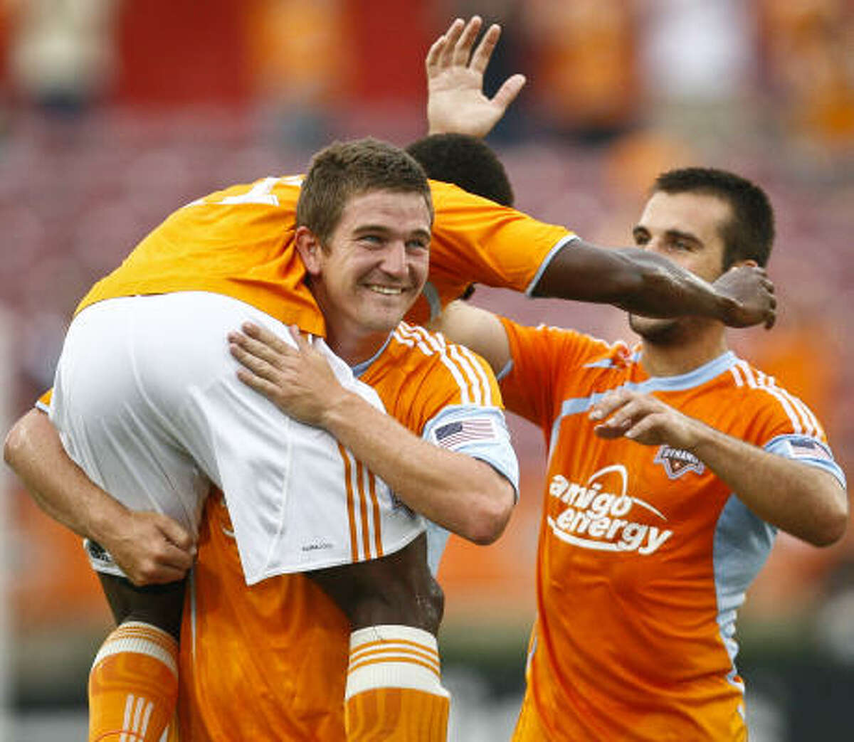 Dynamo midfielder Lovel Palmer is picked up by teammate Bobby Boswell and congratulated by Mike Chabala after Palmer scoring the game's first goal.