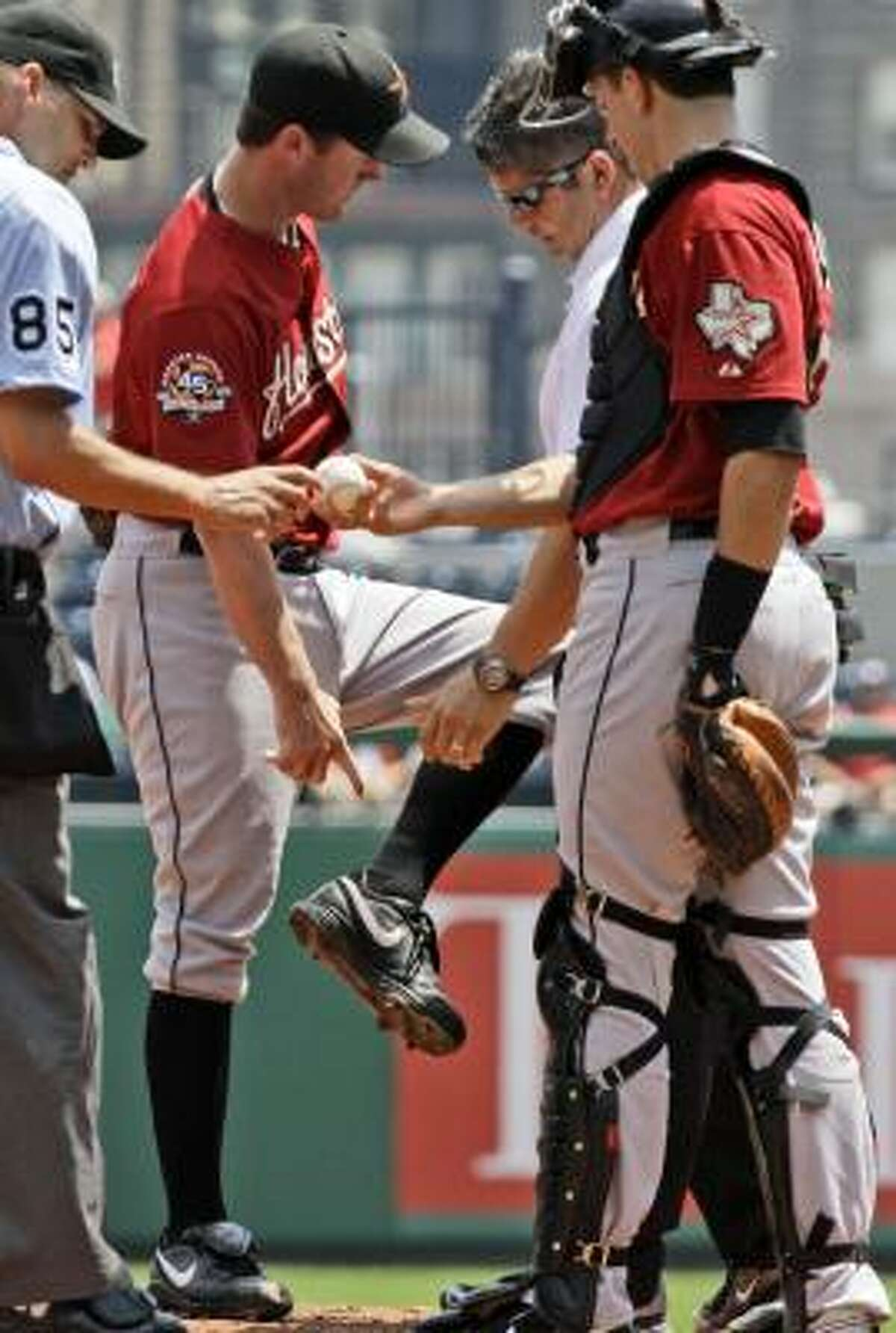 Roy Oswalt points to where a ball hit by Pittsburgh's Pedro Alvarez hit him on the ankle.