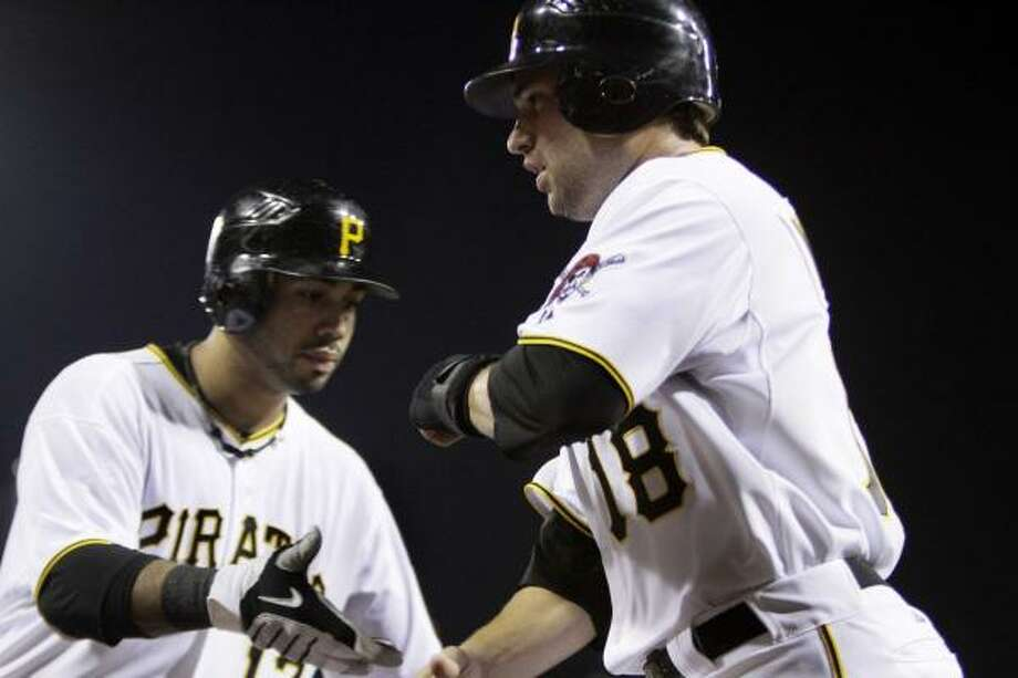 Pittsburgh's Neil Walker, right, is greeted by Pedro Alvarez after scoring on a wild pitch in the sixth inning. Photo: Gene J. Puskar, AP