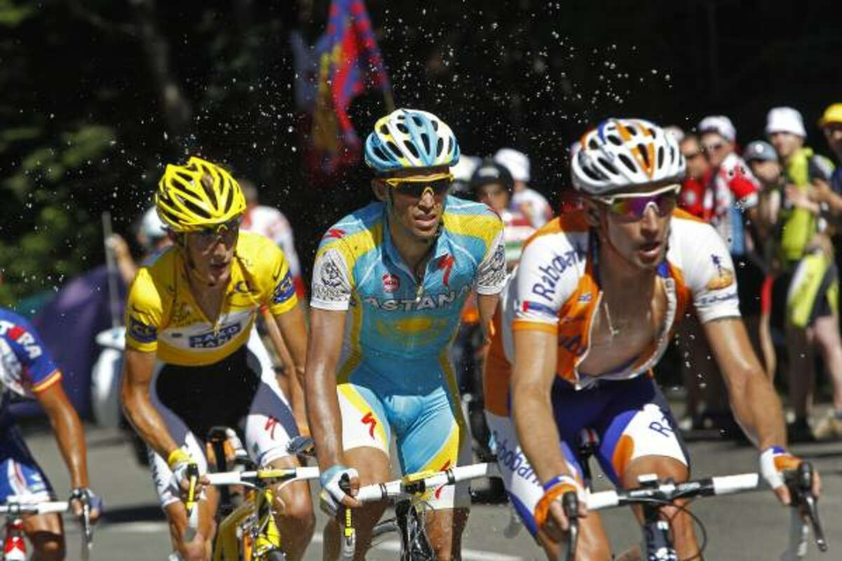 Water is sprayed by spectators as Denis Menchov of Russia, Alberto Contador of Spain, and Andy Schleck of Luxembourg, front to rear, climb the mountains.