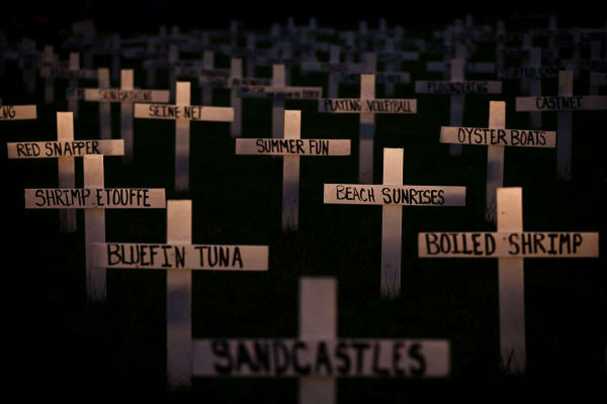 A field of crosses with messages describing summer pastimes 'lost' to the Deepwater Horizon oil spill fills the yard of a home in Grand Isle.