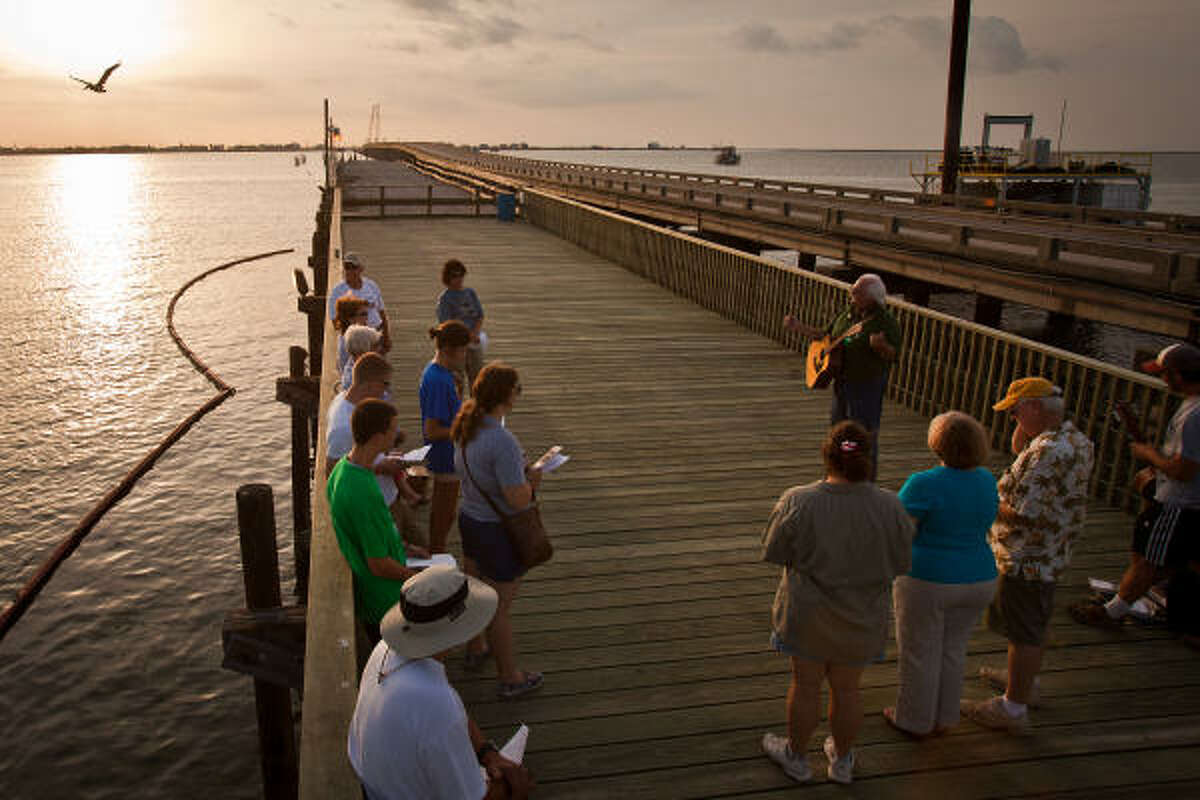 Jim Reid sings for a group of island residents, including Doug and Joyce Miles, far right, during an interfaith prayer service on a fishing pier at sunset in Grand Isle, La.