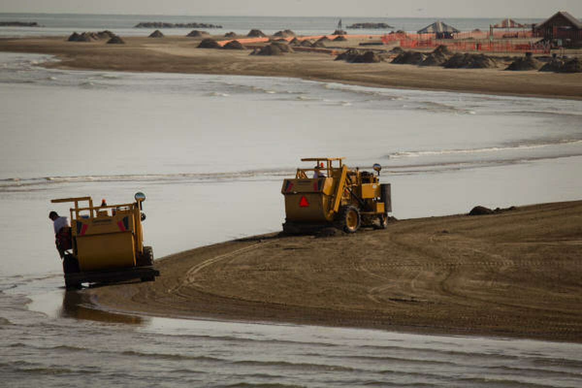 Workers drive beach cleaners to screen sand along the beach at at Grand Isle State Park in Grand Isle, La. The beach remains closed to the public at the park but the campground, lookout and pier remain open.