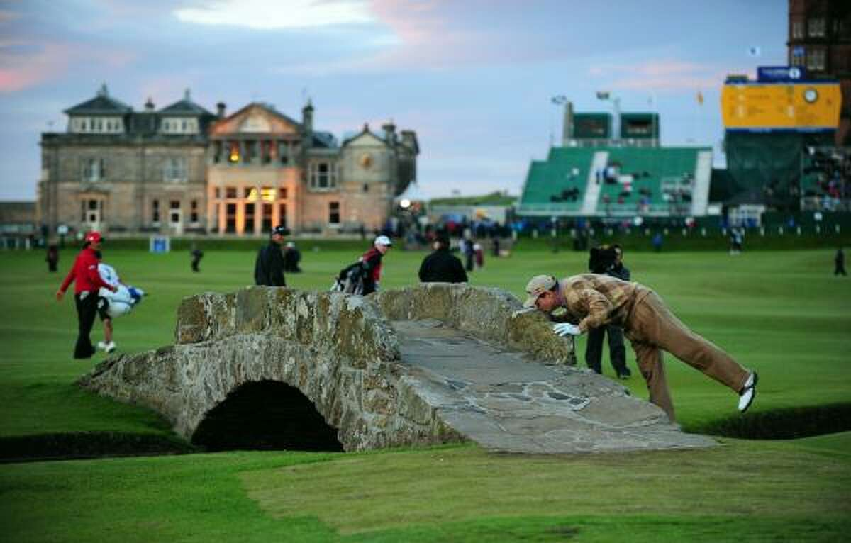 US golfer Tom Watson kisses the Swilcan Bridge in front of the clubhouse on the 18th hole. Watson's 4 over par total will mean he misses the cut, so this will be his last appearance in an Open Championship at St Andrews.